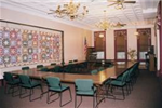 A Town Hall Meeting Room set up with ample tables and seating.