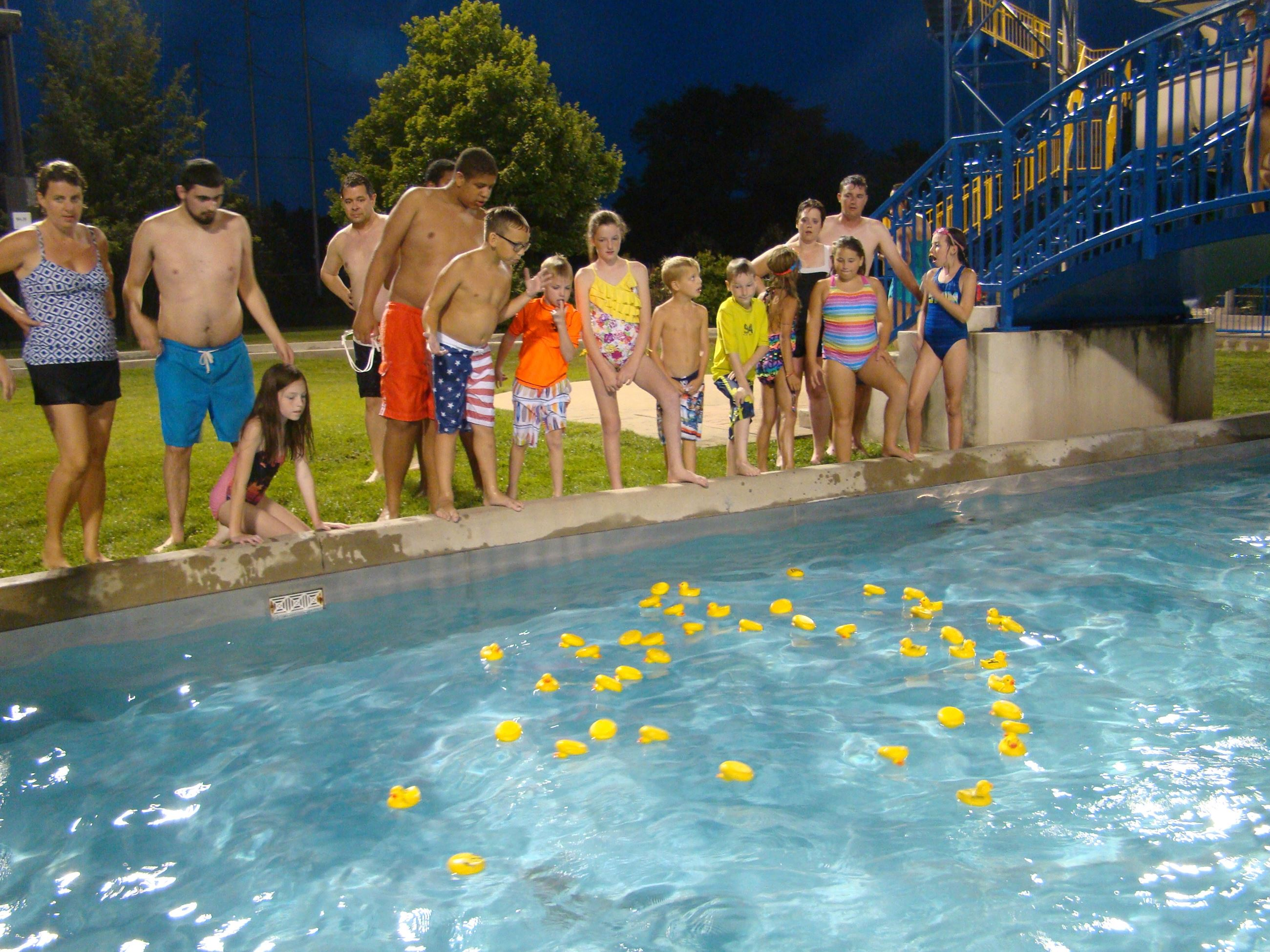 Children enjoying a rubber duck race in the outdoor pool.