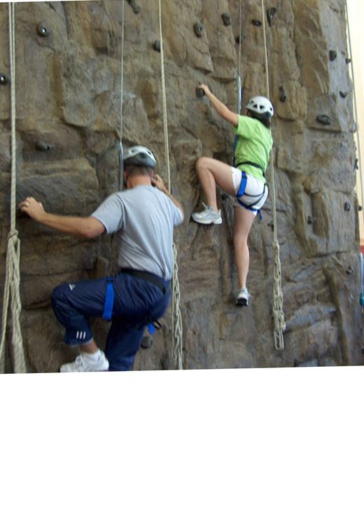 Adults climbing the rock wall.